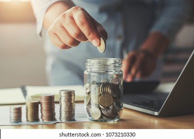 businesswoman hand puting coins in glass for saving money. concept finance and accounting