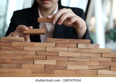 businesswoman hand stacking wood block. growth, success & development in business