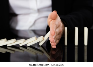 Businesswoman Hand Stopping Dominoes From Falling On Office Desk. Risk Prevention Concept