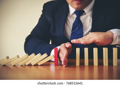 Businesswoman Hand Stopping Dominoes From Falling On Office Desk