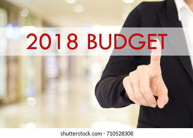 Businesswoman hand touch 2018 budget  button over blur office background with copy space, new year business concept
