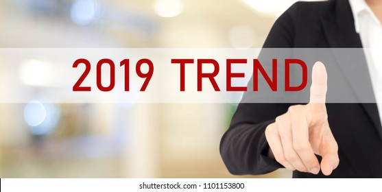 Businesswoman hand touching 2019 trend over blur office background, banner, 2019 business strategy annual plan, success in business concept