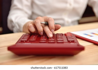 Businesswoman hand using  calculator and expects the companys budget