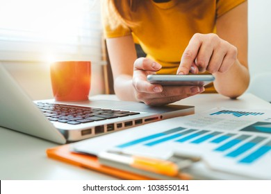 businesswoman hand using smart phone,mobile p payments online shopping,omni channel,digital tablet docking keyboard computer at office in sun light