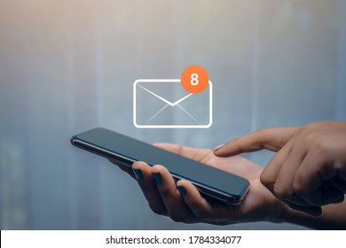 Businesswoman hand using smartphone on table in office with 8 new email alert sign icon pop-up. Mail communication connection message technology. - Shutterstock ID 1784334077