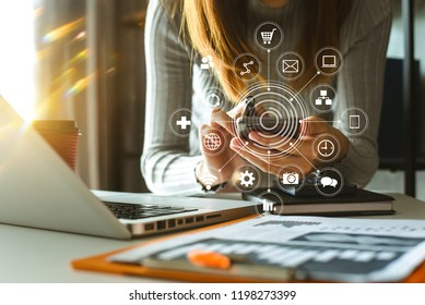 Businesswoman hand working digital marketing media in virtual screen with mobile phone and modern compute with VR icon diagram at office in morning light