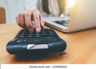 businesswoman hand working with finances about cost and calculator and laptop with tablet on withe desk at office warm colours sun light
