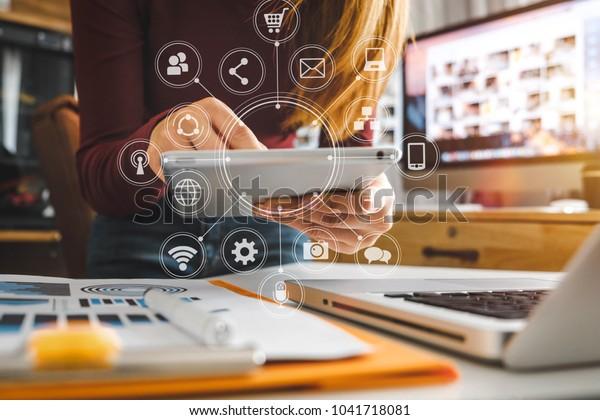 Geschäftsfrau, die mit Laptop-Computer, Tablet- und Smartphone im modernen Büro arbeitet, mit virtuellem Symboldiagramm bei modernoffiim Morgenlicht
