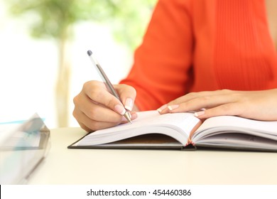 Businesswoman hand writing in agenda on a desk in the office