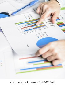 Businesswoman hands analyzing financial statistics. Business woman Meeting Planning Analysis Statistics Brainstorming Concept. Analysis of financial reports. A woman pointing at a colorful chart graph