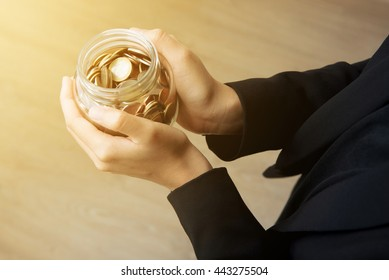 Businesswoman hands holding glass jar with coins