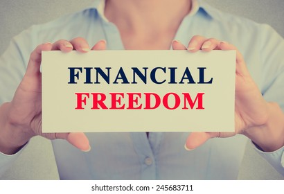 Businesswoman hands holding white card sign with Financial freedom text message isolated on grey wall office background. Retro instagram style image