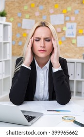 Businesswoman with hands to temples in front of computer. Office at background. Concept of headache.