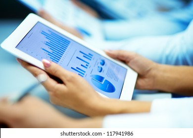 Businesswoman hands with touchpad while learning situation on the market