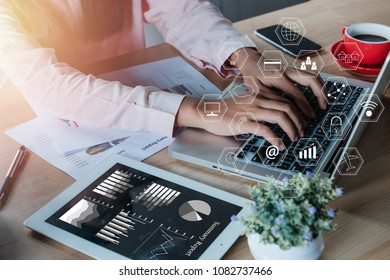 Businesswoman hands typing on keyboard in office with virtual graphic icon diagram