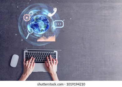 Businesswoman hands using laptop with abstract globe hologram on wooden background. Global business concept. Elements of this image furnished by NASA