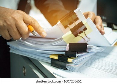 Businesswoman hands working on Stacks of documents files for finance in office. Business report papers or Piles of unfinished document achieves with black clip paper.Concept of Business Annual Reports