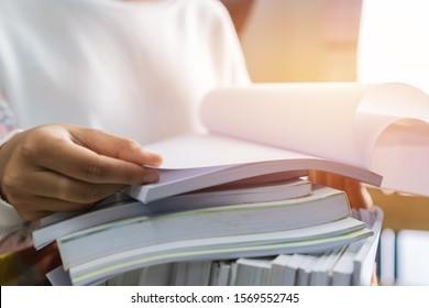 Geschäftsleute, die in Papierstapeln arbeiten, um Informationen über die Arbeitstischabteilung zu finden, Geschäftsberichte, Haufen unfertiger Dokumente, die mit Videos im Inneren erreicht werden,Geschäftskonzept