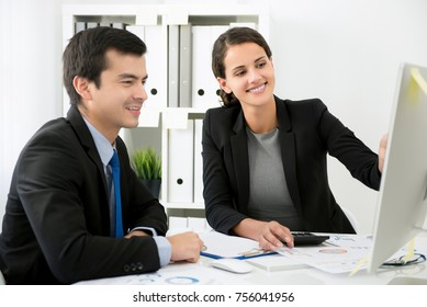 Businesswoman happily training new male staff member with desktop computer in the office
