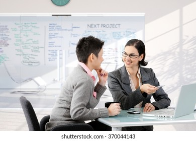 Businesswoman having discussion at work sitting at office desk, smiling.