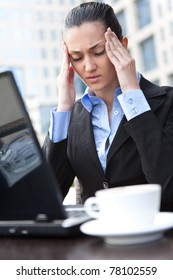 businesswoman having headache in front of her laptop, expression face