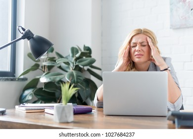 businesswoman having headache and touching head with hands