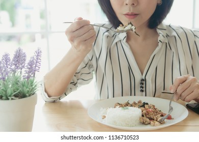 Businesswoman having lunch at restaurant sitting at table eating Basil Fried Rice Chicken without oil