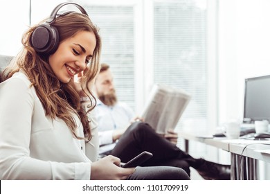 Businesswoman with headphones sitting at desk during the break and using mobile phone while man is reading newspaper