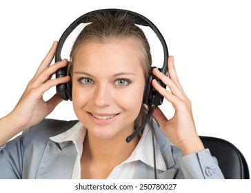 Businesswoman in headset with her hands on headset speakers, looking at camera, smiling. Isolated over white background