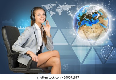 Businesswoman in headset, sitting on office chair, her hand on microphone, looking at camera, smiling. Globe, world map, communication network and other virtual elements as backdrop. Element of this