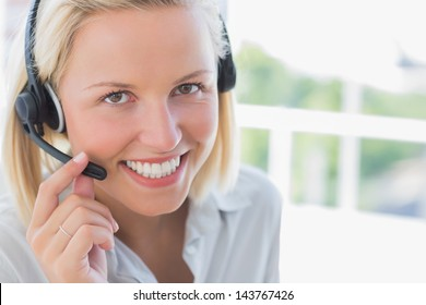 Businesswoman with headset smiling at camera in her office