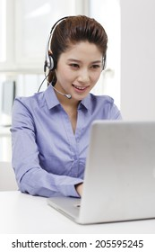 Businesswoman with headset using a laptop
