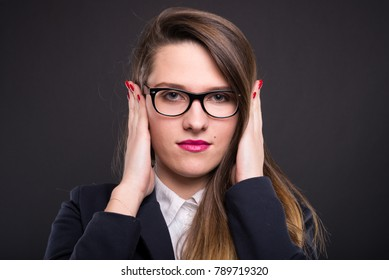 Businesswoman in the hear no evil pose looking at the camera with covered ears