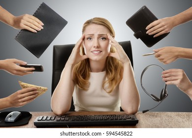 businesswoman at her desk looking worried with her hands up to her head, surrounded by many hands with different objects in each hand