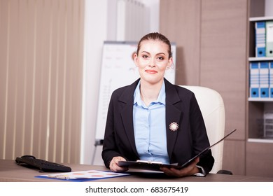 Businesswoman in her office looking in a folder with charts