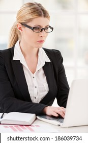 Businesswoman at her working place. Serious mature woman in formalwear working on laptop while sitting at her working place