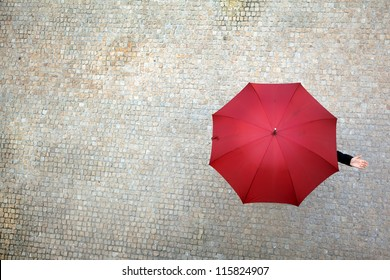 Businesswoman hidden under umbrella and checking if it's raining