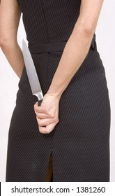 Businesswoman hide a kitchen knife behind her back