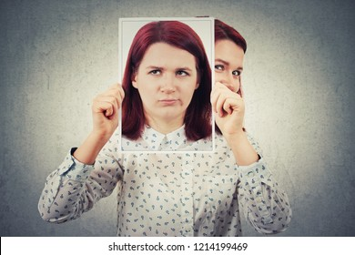 Businesswoman hiding face behind a photo sheet portrait with frustrated emotion.Undercover like a mask to hide real personality and create a fake identity.