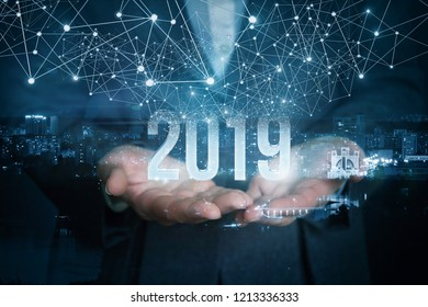 A businesswoman is holding the 2019 year numbers inside the night city image picture with distinct wireless connections above.
