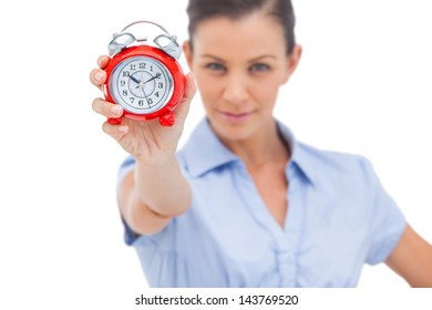 Businesswoman holding alarm clock and looking at the camera