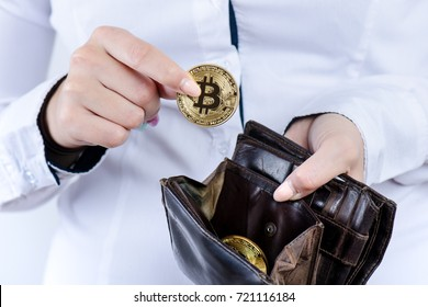 Businesswoman holding bitcoin isolated on a white background.Golden bitcoin coins in women's hands. Virtual currency. Crypto currency. New virtual money. Opened wallet.