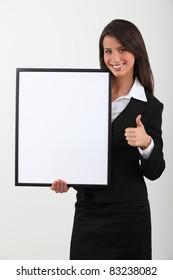 Businesswoman holding blank message board