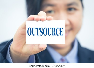 Businesswoman holding card with OUTSOURCE message.