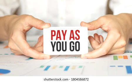 businesswoman holding a card with text PAY AS YOU GO