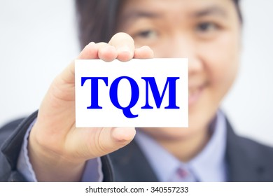Businesswoman holding card with TQM message.
