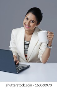 Businesswoman holding a coffee mug and using a laptop