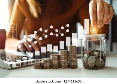 businesswoman holding coins putting in glass with using smartphone and calculator to calculate  concept saving money for finance accounting
