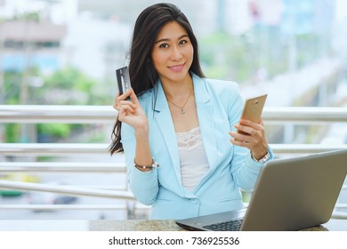 Businesswoman holding a credit card and using smart phone office background,Shopping Online Concept.
