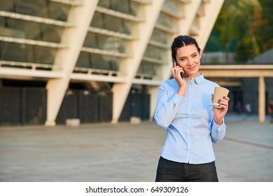 Businesswoman holding cup and phone. Caucasian female smiling. Post interview call back rules.